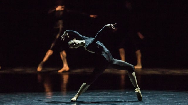 Ein Tänzer in schwarzen Kleidern verbiegt sich nach hinten
