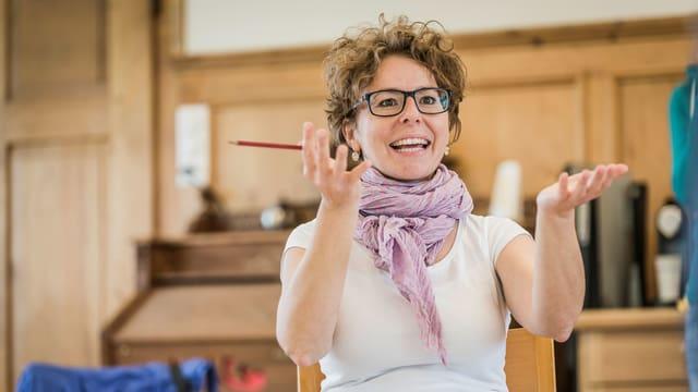 Eine Frau mit Brille sitzt auf einem Stuhl und scheint mit ihren Händen zu sagen: bitte mehr!