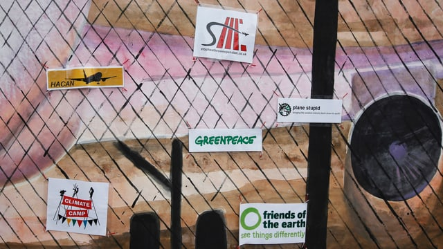 Zaun am Flughafen Heathrow mit Stickern von Umweltorganisationen
