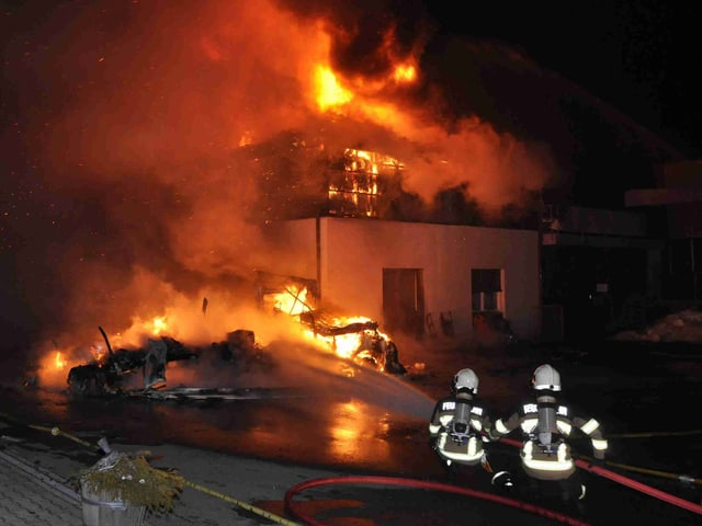 Zwei Feuerwehrmänner spritzen in eine Feuer