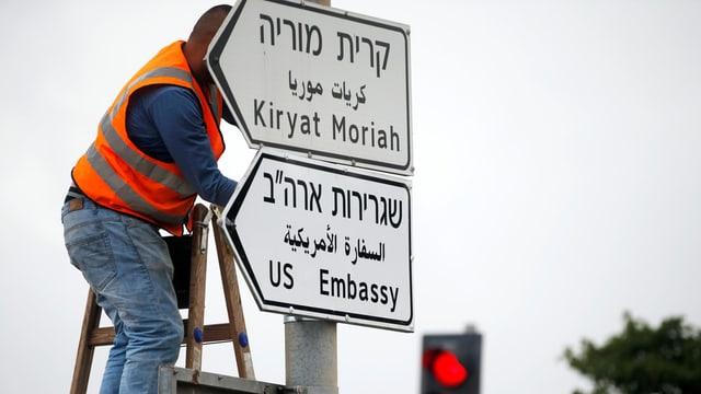 Ein Mann montiert das Strassenschild für die US-Botschaft in Jerusalem.