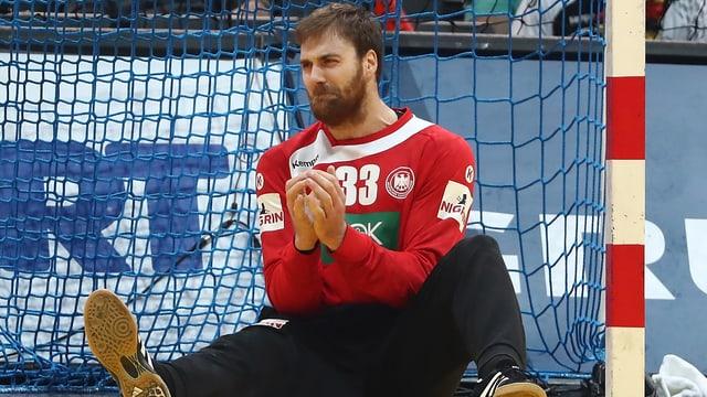 Andreas Wolff sitzt frustriert auf dem Hallenboden.
