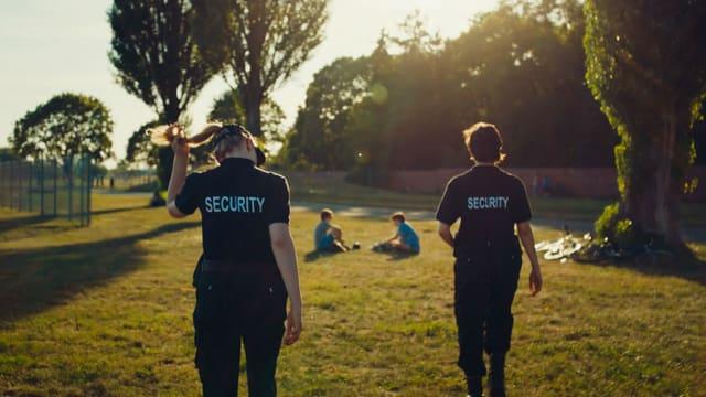 Zwei junge Frauen in Scurity-Uniformen im Park.