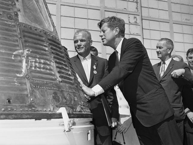 John F. Kennedy (Mitte) schaut in die Mercury-Kapsel, daneben John Glenn (links) und Lyndon B. Johnson (rechts)