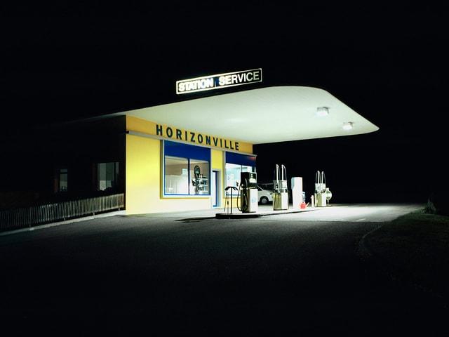 """Eine hell beleuchtete, kleine Tankstelle mit zwei Zapfsäulen bei Nacht. An der Fassade steht """"Horizonville""""."""