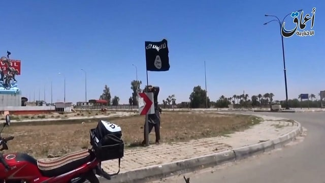 In cumbattant da la gruppa da terror Stadi islamic plazzescha ina bandiera.