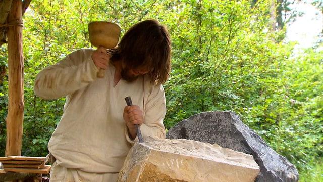 Mann in Jutehemd schlägt mit Holzhammer auf Meissel.