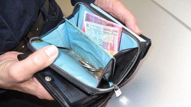 Ein offenes Portemonnaie mit wenig Geld.