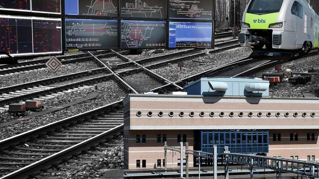 Ein Bild mit der Betriebszentrale Spiez, Gleisanlage und Monitorwand.