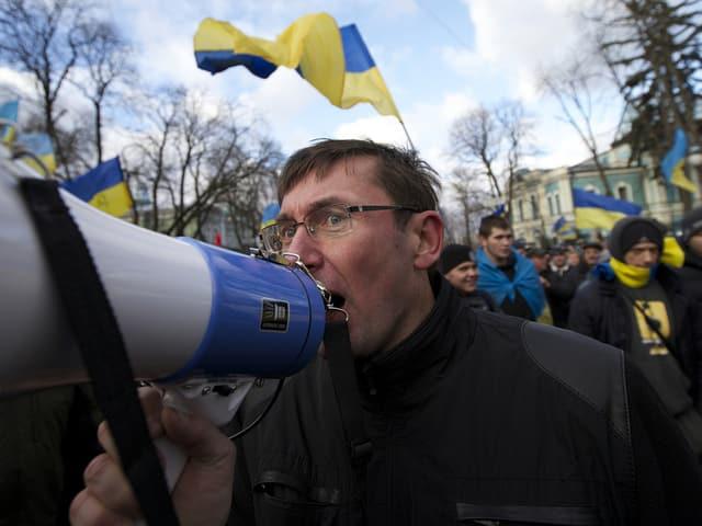 Mann mit Megaphone im Protestzug.