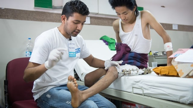 Ein Arzt behandelt das Bein eines Jugendlichen.