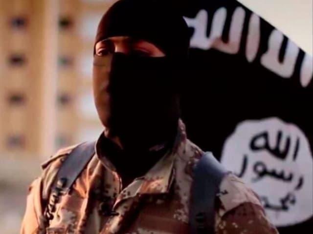 IS-Kämpfer vor Flagge