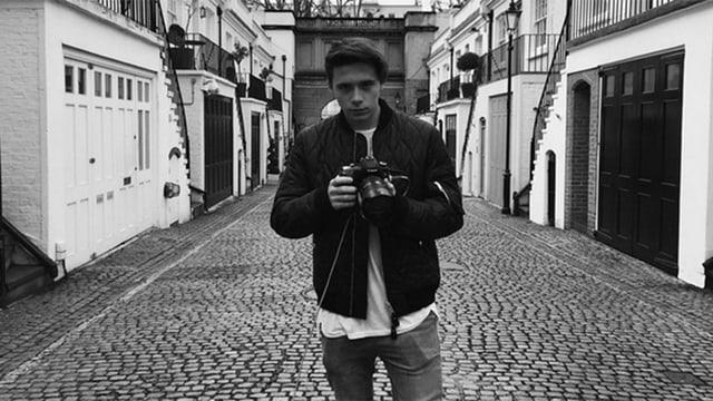 Brooklyn Beckham steht auf der Strasse und hält eine Kamera in der Hand.