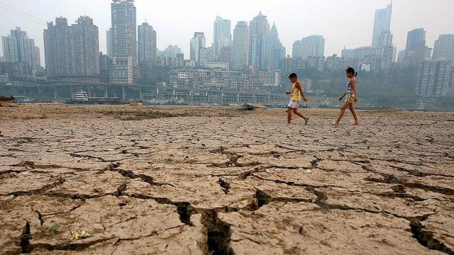 Kinder vor chinesischer Stadt auf vertrocknetem Boden.