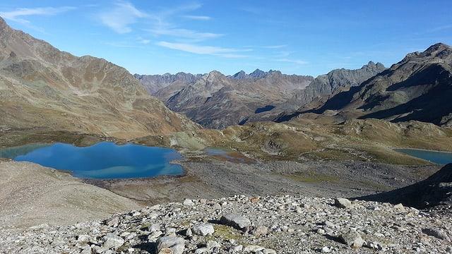 Berglandschaft mit blauen Bergseen, darüber leicht bewölkter Himmel.