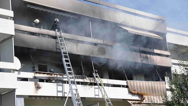 Mehrfamilienhaus. Rauch steigt auf. Feuerwehrleitern sind an die Balkone angelehnt.