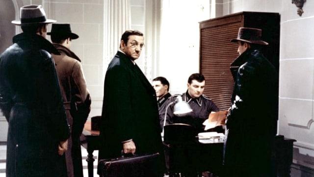 Ein Mann mit Koffer steht zwischen vier anderen Männern.