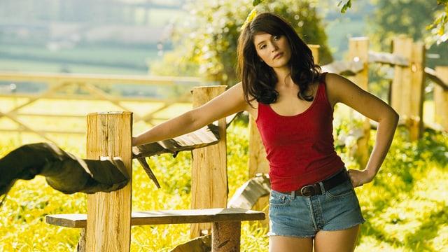 Eine leich bekleidete junge Frau steht an einem Holzzaun in einer ländlichen Region.