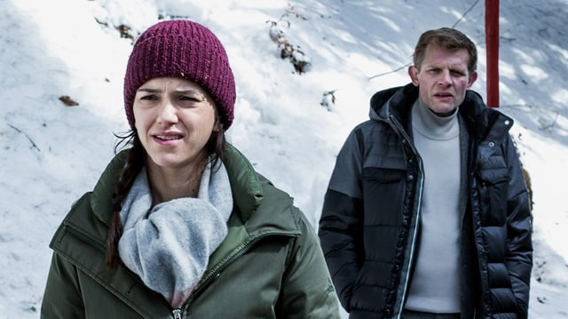 Eine frau und ein Mamm in Winterkleidung stehen in einer verschneiten Landschaft.