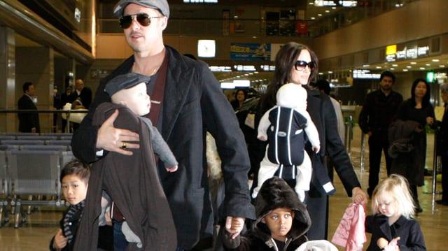 Brad Pitt und Angelina Jolie laufen mit ihren Kindern am Flughafen entlang, Er geht vor, sie kommt nach.