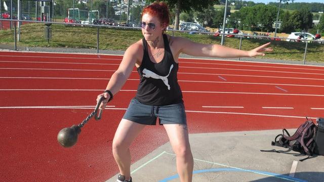 Eine Frau wirft eine Distance-Kugel auf einem Sportplatz.