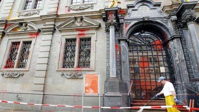 Das Zürcher Rathaus, überall rote Flecken, davor ein Mann in gelben Hosen mit Schlauch, der putzt.