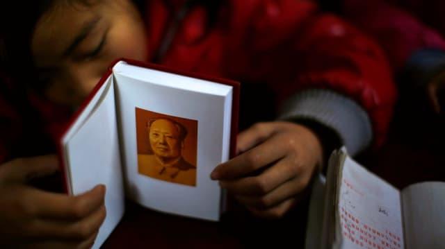 Chinesisches Mädchen hält Buch, darin ein Bild von Mao.