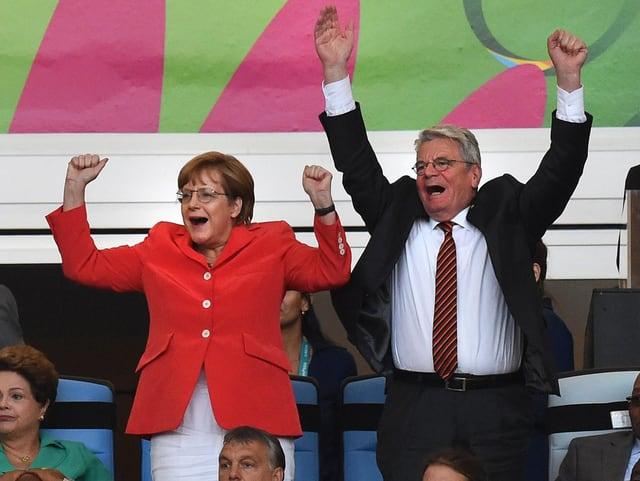 Angela Merkel und Joachim Gauck jubeln.