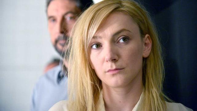 Eine blonde Frau steht im Vordergrund, hinter ihr ein unscharfer Mann.