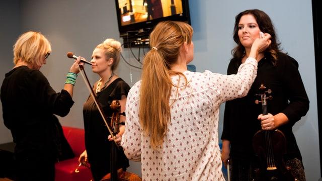 Musikerinnen werden vor dem Auftritt gepudert.