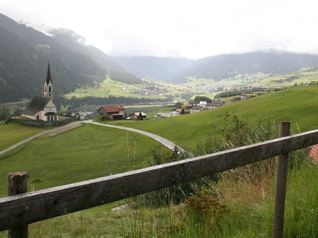Ein Holzgeländer im Vordergrund, im Hintergrund Wiesen, Wälder, Berge und ein Dorf mit Kirche.