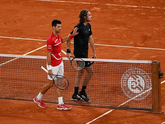 Novak Djokovic und Stefanos Tsitsipas begegnen sich am Netz.
