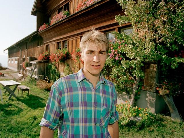 Junger Mann vor Bauernhof.