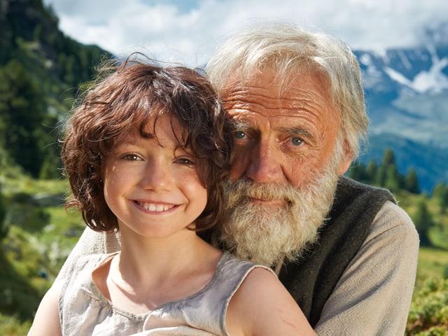 Alter Mann umarmt Kind in den Bergen.