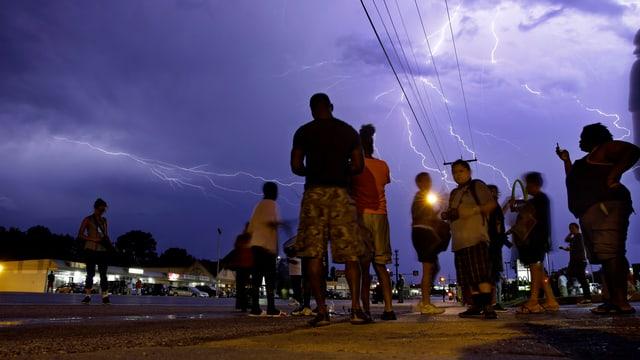 Menschengruppe auf der Strasse. Blitze am Himmel