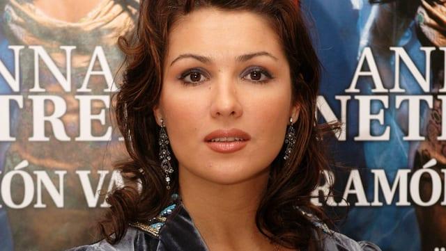 Anna Netrebko posiert vor einem Plakat.