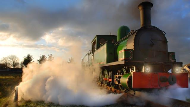 Nahaufnahme einer fahrenden Dampflokomotive.