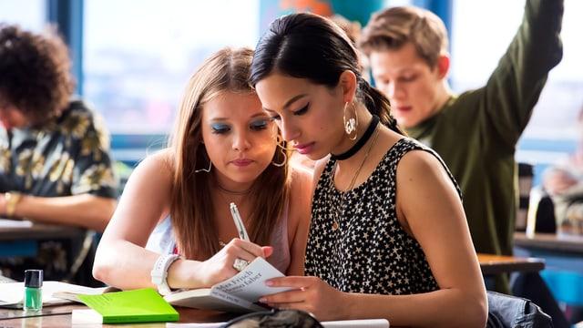 Zwei Mädchen sitzen in einem Schulzimmer am Pult und schauen gemeinsam in ein Buch.