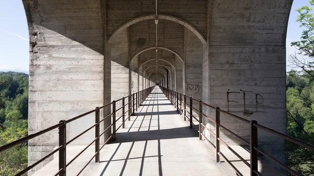 Eine Brücke, die zur Hälfte mit Schatten bedeckt ist.
