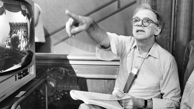 Schwarz-Weiss Fotografie des Regisseurs, der ein Mikrofon um den Hals trägt, einen Notizbock auf den Knien liegend hat und mit einem ausgestreckten Arm Anweisungen gibt.
