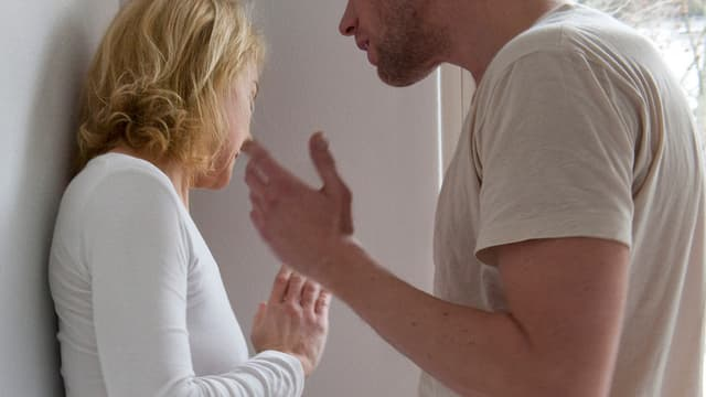 Ein Mann erhebt die Hand, Frau steht gegen eine Wand und schaut weg.
