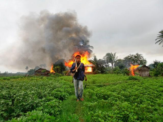 Militanter Buddhist mit Waffe, dahinter ein brennendes Haus.