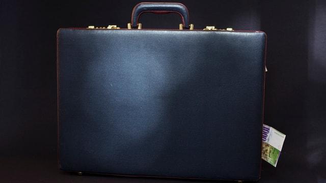 Bild eines schwarzen Koffers mit einem eingeklemmten Geldschein.