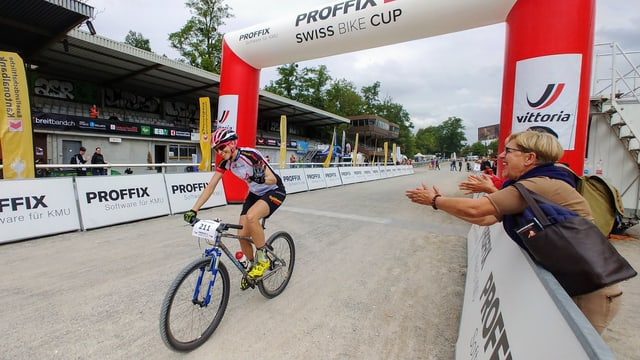 Katrin Leumann fährt auf Mountainbike ins Ziel