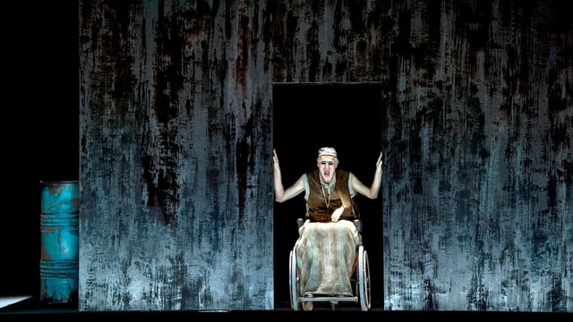 Ein Mann in einem Rollstuhl in einem dunkel ausgeleuchteten Bühnenbild.