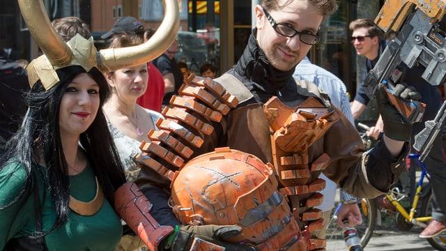 Ein Mann trägt eine riesige Rüstung, neben ihm steht eine Frau, die goldene Hörner trägt.
