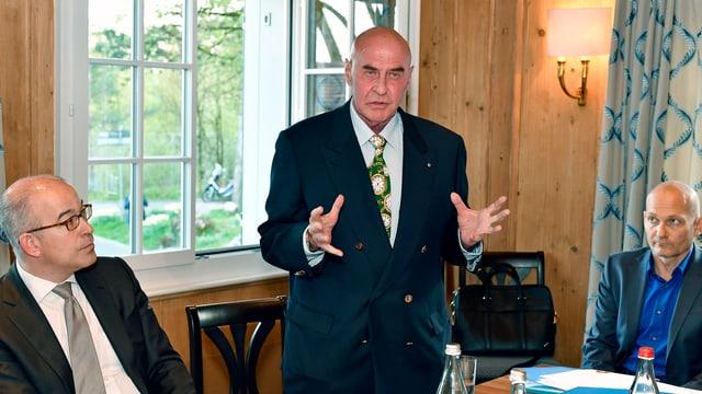 Ein Politiker hält stehend eine Rede, zwei Männer hören ihm sitzend zu