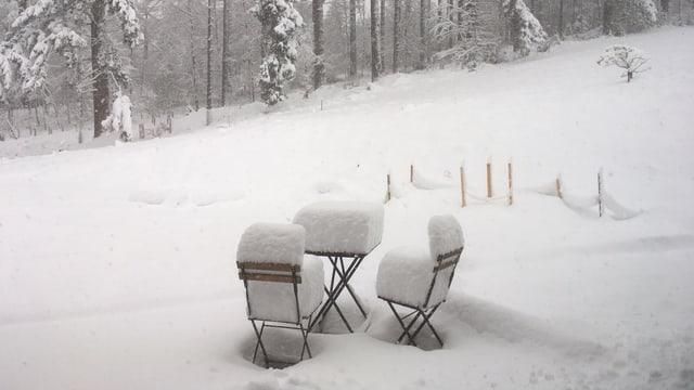 Schnee auf Stühlen und Gartentisch in der Nähe eines Waldrandes.