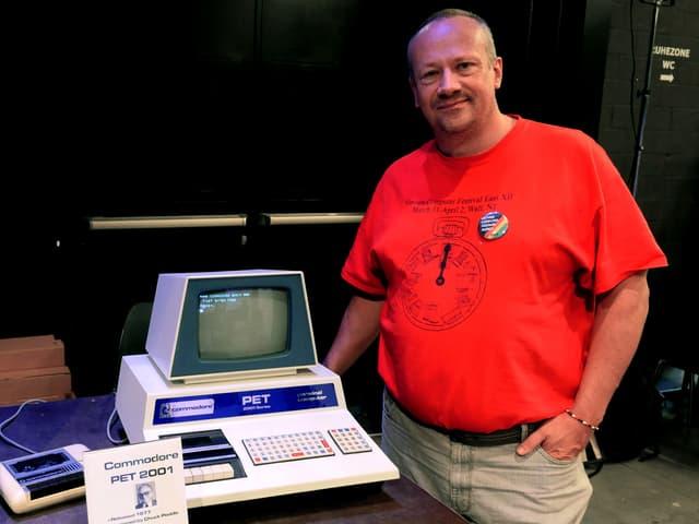 Mann zeigt einen alten Computer.