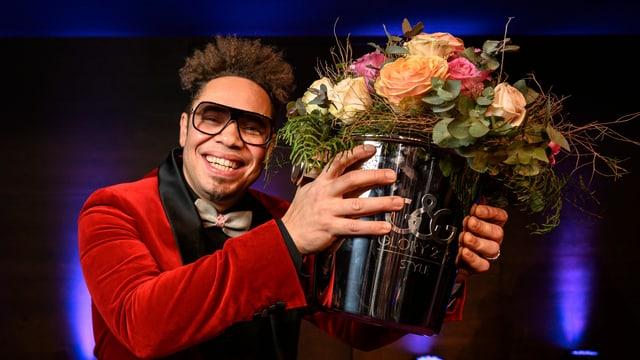Mann in rotem Jackett mit Blumenstrauss in der linken Hand